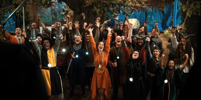 The cast of Mythic Quest in medieval fantasy costumes all cheer.