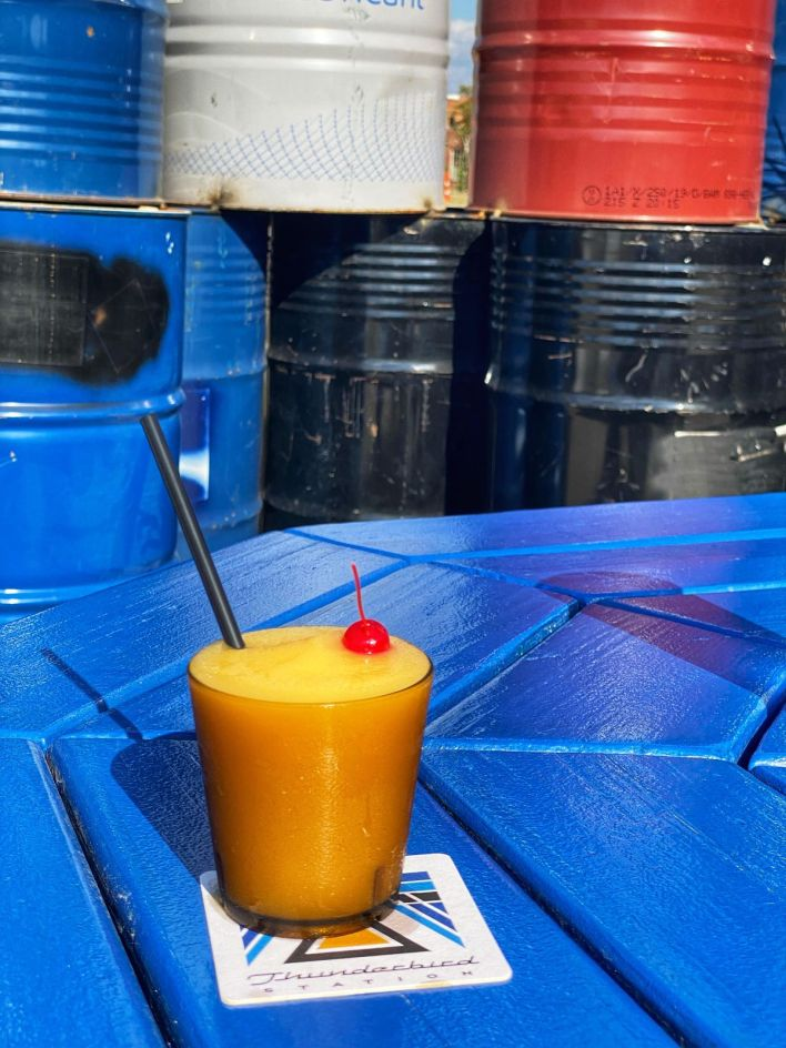 A yellow frozen cocktail served in an amber glass and garnished with a maraschino cherry. The drink is sitting on a blue slatted picnic table.