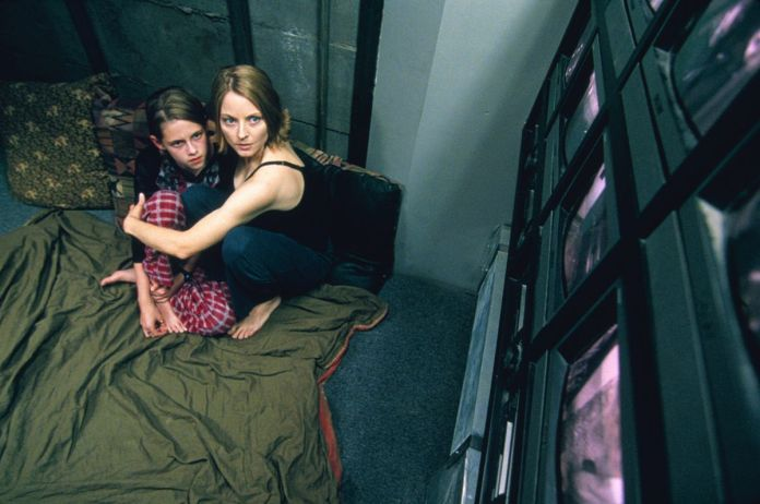 Jodie Foster and Kristen Stewart huddle on a green blanket while watching a wall of screens in Panic Room.