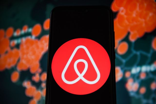 In this photo illustration an Airbnb logo is seen displayed...