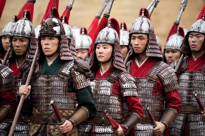 Mulan stands among a group of soldiers in the Mulan remake