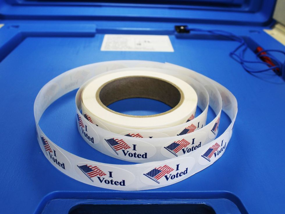 "A roll of ""I voted"" stickers designed with the American flag is placed on the writing surface of a blue voting booth."