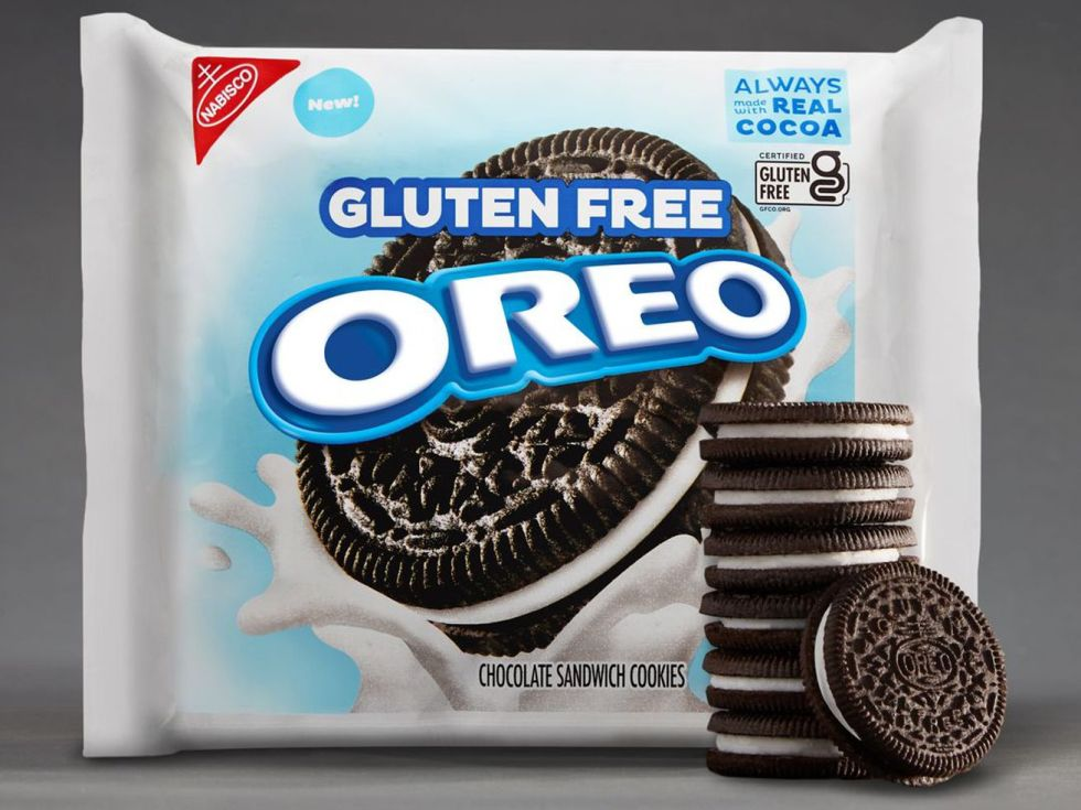 A white package of gluten-free Oreos against a gray background, with a stack of Oreo cookies in front of it.