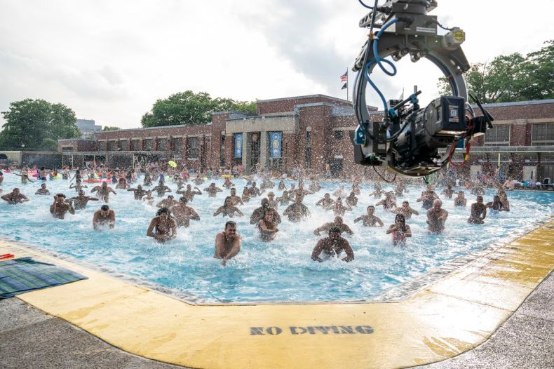 A group of swimmers in a community pool, with a camera rig in the foreground.