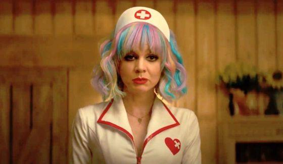 Seorang wanita muda berkulit putih dengan rambut bergaris pelangi dengan kostum perawat menatap ke depan dengan muram.