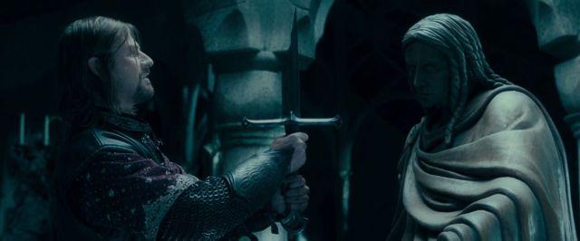 Sean Bean como Boromir levanta la espada rota Narsil con una leve sonrisa en The Fellowship of the Ring