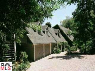 Une maison avec un toit brun foncé entouré d'arbres.