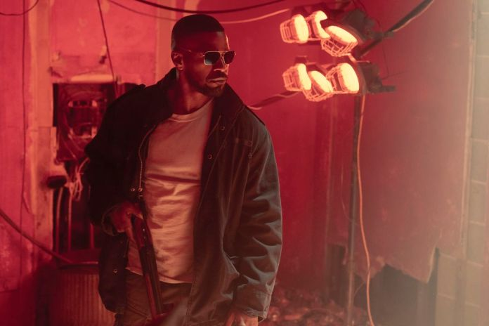 Jamie Foxx wearing sunglasses and carrying a shotgun in Project Power