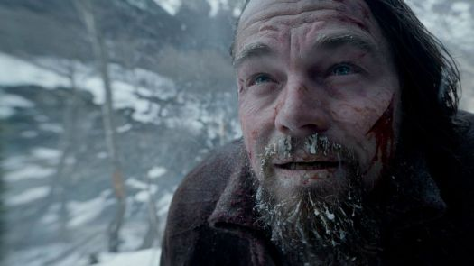 A close-up ofLeonardo DiCaprio's face, streaked with blood, a deep open cut across one cheek, with his beard, mustache, and eyebrows filled with chunks of ice.