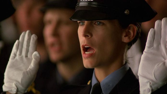 Jamie Lee Curtis, in police uniform and white gloves, takes an oath in a group of other police in Blue Steel.