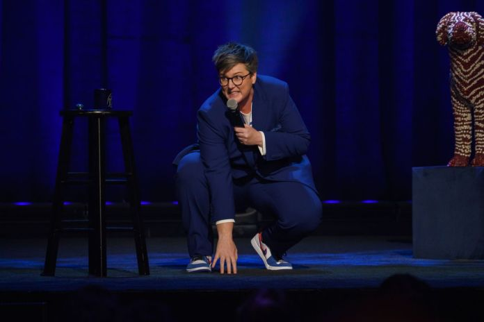 Hannah Gadsby crouches down to touch the floor with a mic in her hand in Douglas
