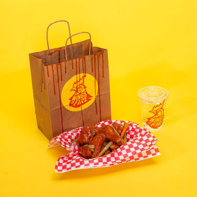 A bag with a sticker for a fake brand called Wings of Fire next to a basket of chicken wings and a clear plastic cup with another sticker for Wings of Fire on a yellow backdrop.