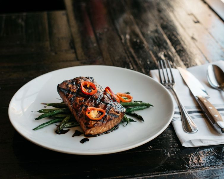 A round white plate holds a piece of grilled salmon over a small pile of green beans