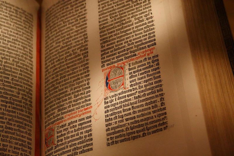 "Detail of a page from the Gutenberg Bible, showing a large illustrated letter ""E"" styled next to the main text"