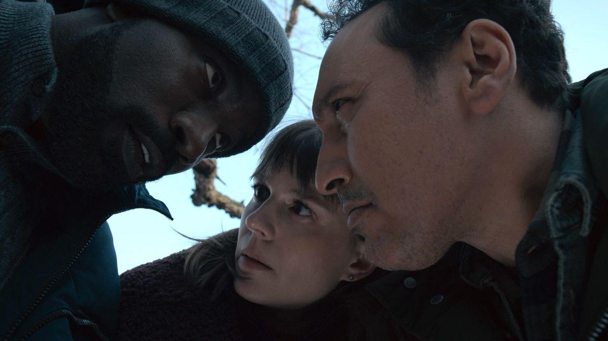 David (Mike Colter), Kristen (Katja Herbers), and Ben (Aasif Mandvi) huddle together whispering in Paramount Plus' Evil