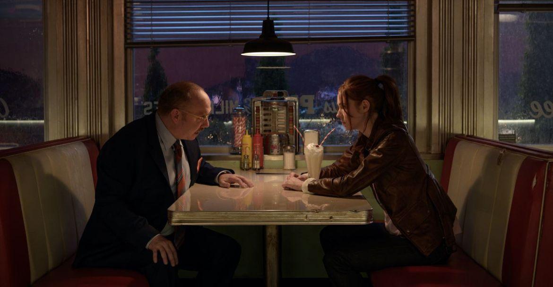 Paul Giamatti sits opposite Karen Gillan in a nighttime diner scene from Gunpowder Milkshake
