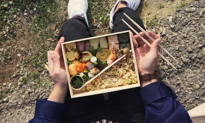 A bento box with two compartments is filled with artfully designed foods, sitting on the lap of a person holding chopsticks.