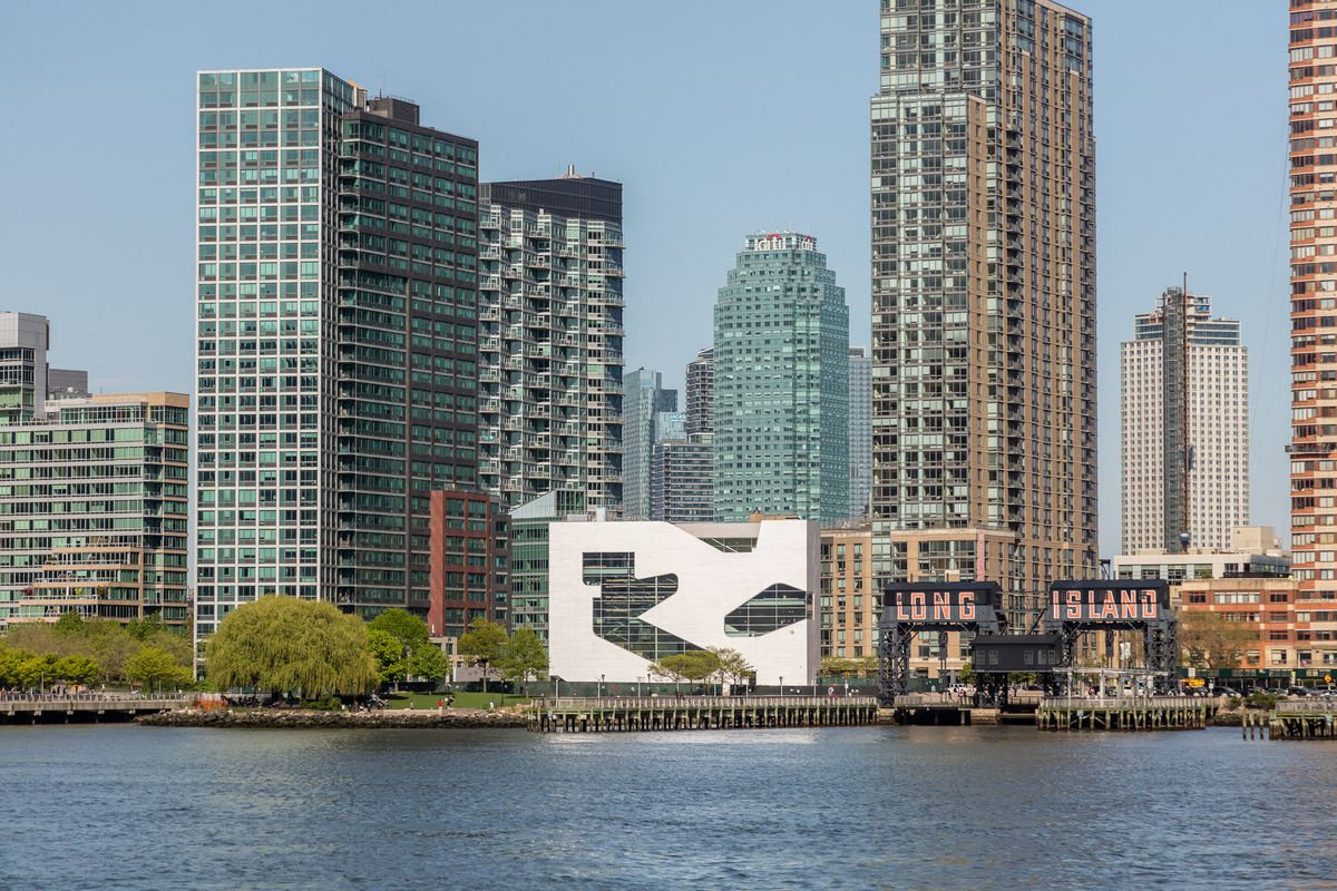The Hunters Point Library, a modern, white building with odd-shaped windows, on the bank of the East River, with the skyscrapers of Hunters Point and Long Island City rising behind the library. This view is from the Manhattan side of the river. Photo credit: Max Touhey, via Curbed NY