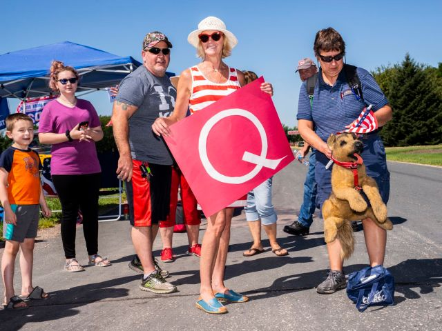 A person holding a sign with a large letter Q stands with a group of people at a roadside.