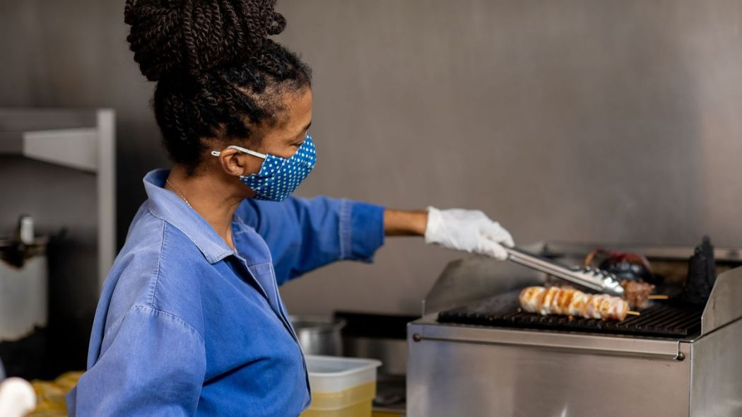 Natalia Pereira, chef and owner of Wood Spoon restaurant in Downtown LA, wearing a cloth mask and grilling meats in the kitchen.