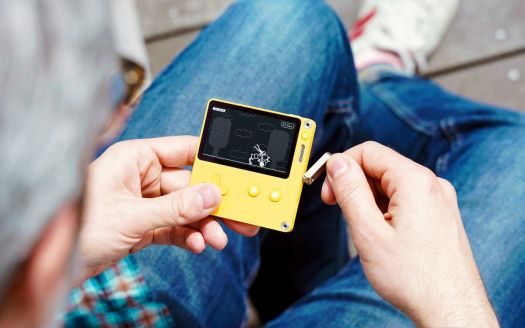 A photo of a man playing a game on Playdate
