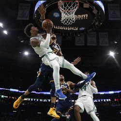 Boston Celtics' Marcus Smart is knocked off balance while going for a shot against Utah Jazz's Rudy Gobert (27) during the fourth quarter of an NBA basketball game Friday, March 6, 2020, in Boston.