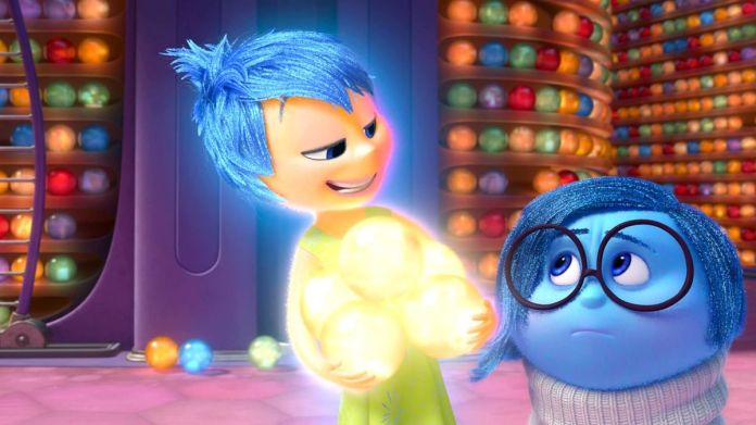 a yellow figure representing joy holds glowing orbs next to a blue figure representing sadness