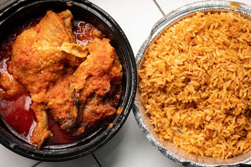 Bowl with stewed chicken sits next to aluminum container filled with jollof rice.