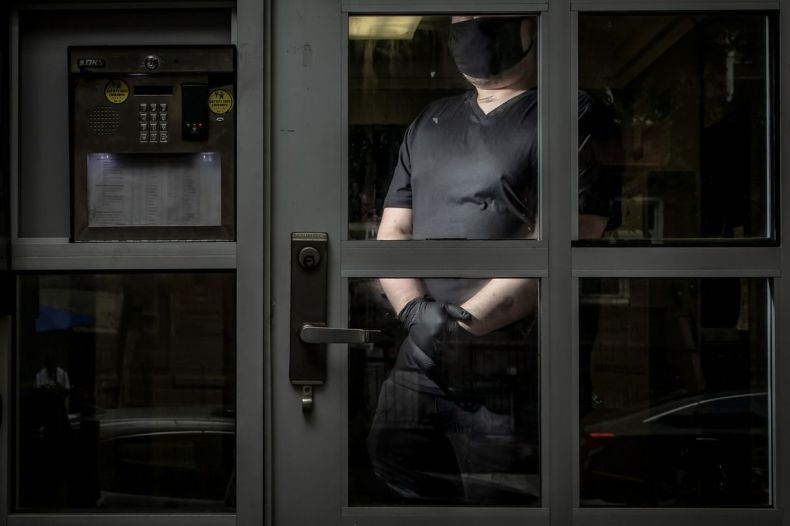 A man wearing a face mask stands behind a glass door entryway to his apartment building