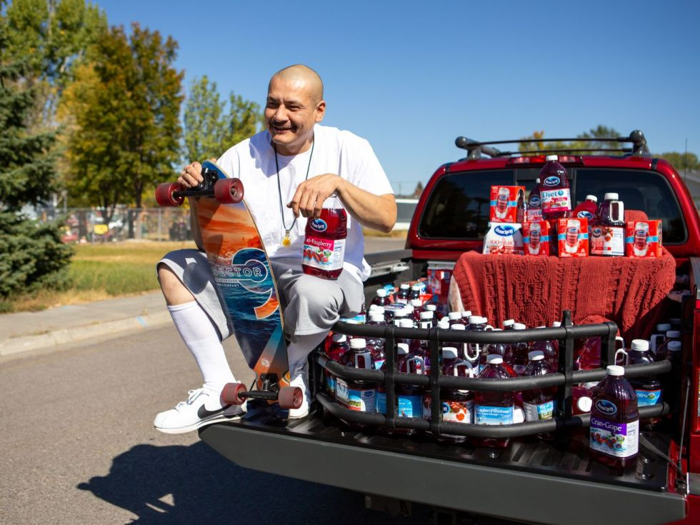 A bald man in a white t-shirt crouches in the bed of a red truck while holding an Ocean Spray branded skateboard and surrounded by bottles of cranberry juice.