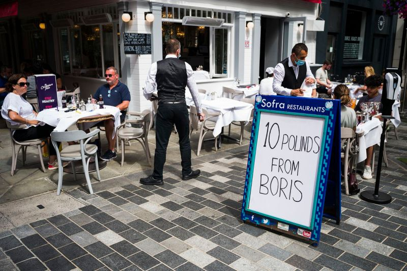 """A sandwich board outside a restaurant where there are outdoor tables and diners, reads, """"10 pounds from Boris."""""""