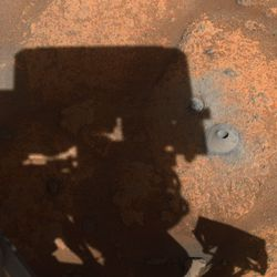 The hole Perseverance drilled on August 5th sitting to the right of the shadow of the rover's turret.
