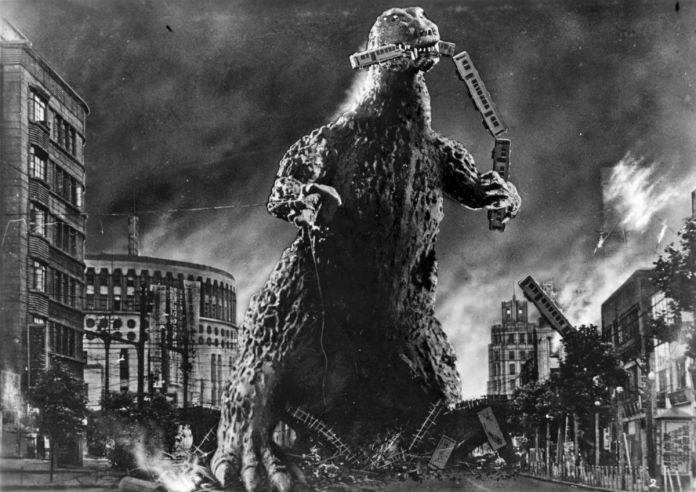 Godzilla tears a line of train cars apart with his teeth
