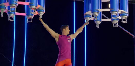 a man hangs from two sets of rotating rings in ultimate beastmaster