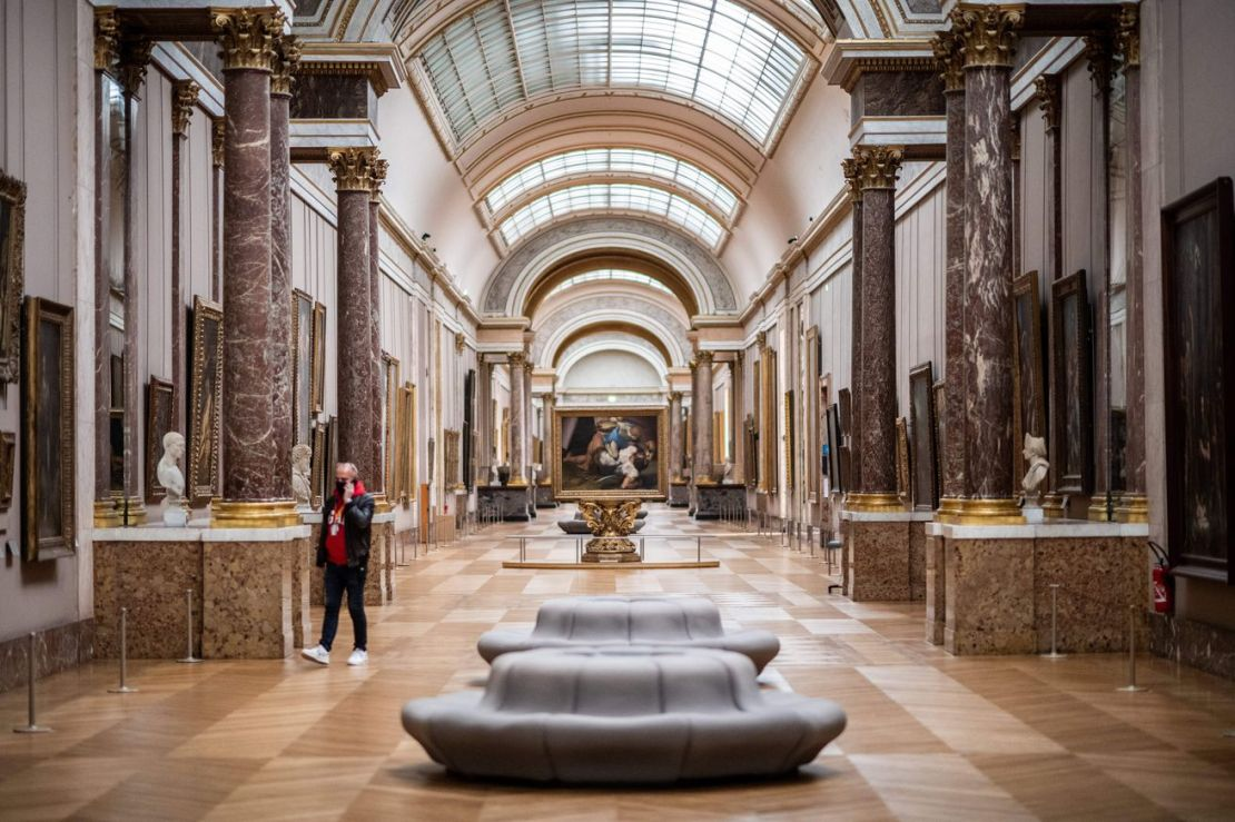 A spacious, sunlit gallery hall at the Louvre, with skylights, marble pillars, and artworks along the walls.