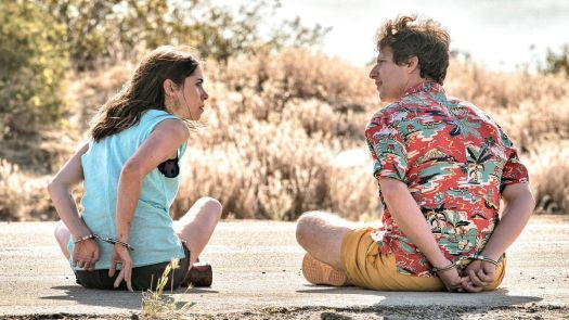 Andy Samberg and Cristin Milioti sit on the side of the road in handcuffs in Hulu's Palm Springs.