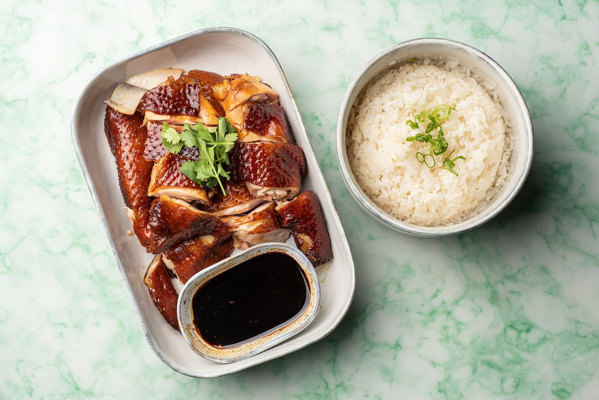 Un plato de pollo dorado servido con un plato de arroz.