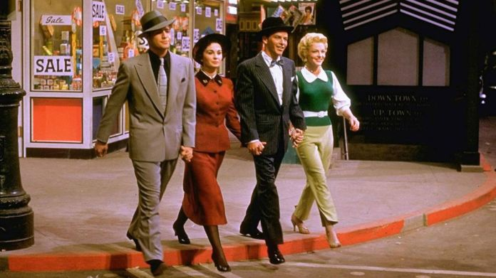 Marlon Brando, Jean Simmons, Frank Sinatra, and Vivian Blaine holds hands walking down the street