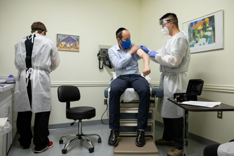 Rabbi Shmuel Herzfeld has his arm disinfected by Dr. Chao Wang as Jake Bart, an unblinded verifier, looks on, during a clinical trial at Meridian Clinical Research in Rockville, Maryland on Monday.