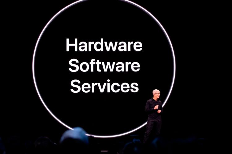 "Tim Cook in front of a slide that reads ""hardware software services"""