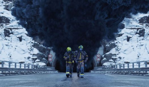 Two firefighters walking out of tunnel obscured behind a plume of smoke