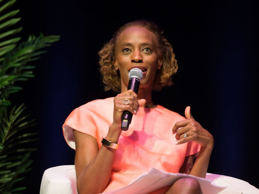 Dawn Davis wears a pink organza dress while seated in a light gray chair and speaking into a microphone.