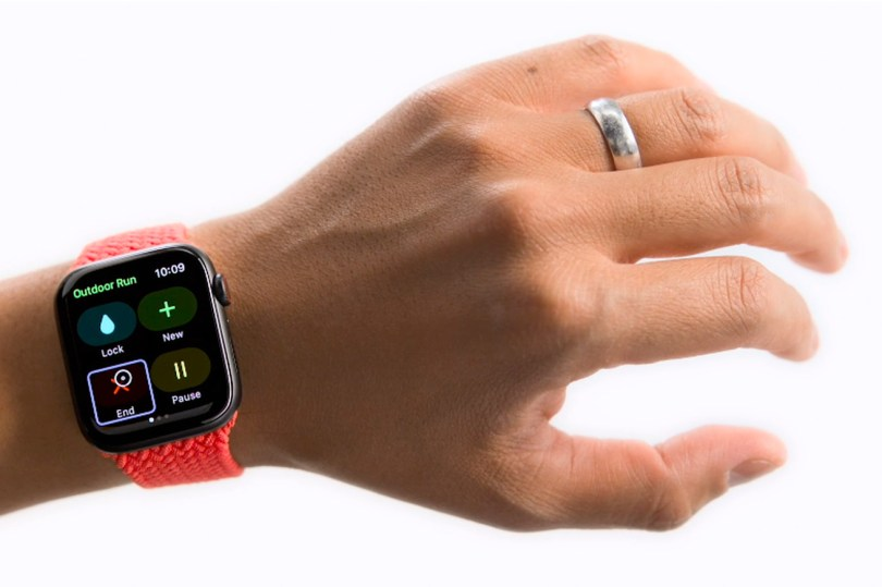 A person's wrist showing an Apple Watch. On the screen of the Watch is an option to end a run, highlighted with a small cursor hovering over it.