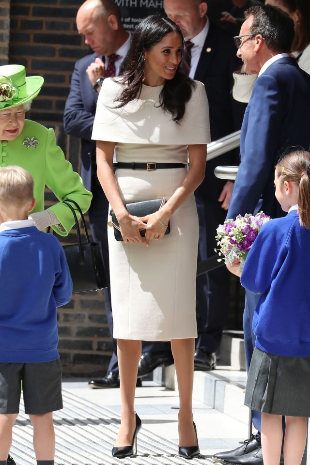 Markle greets people while standing next to the queen.