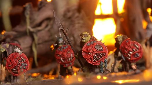 A group of Orruks lit by firelight.