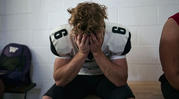 A football player in uniform slumps on the bench with his head in his hands in Last Chance U: Laney