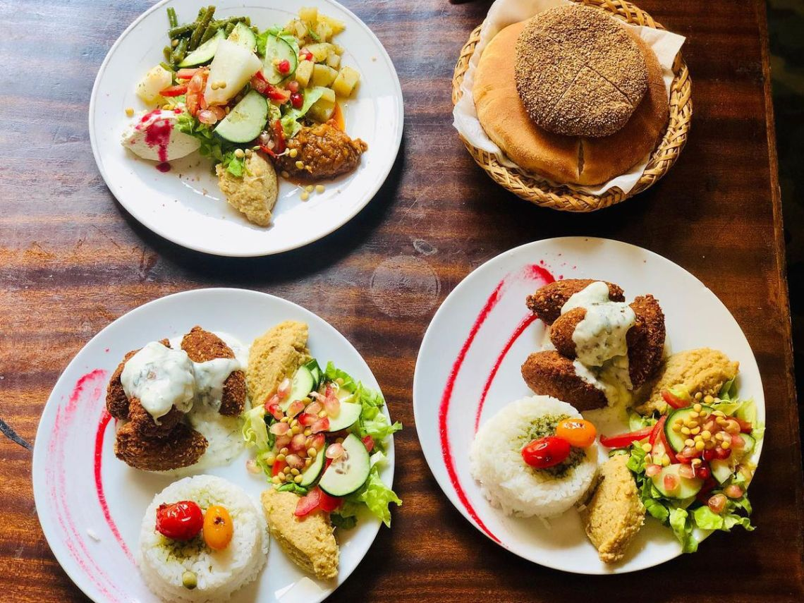 From above, dishes on a wooden table including flatbreads, various preparations of falafel, and vegetables