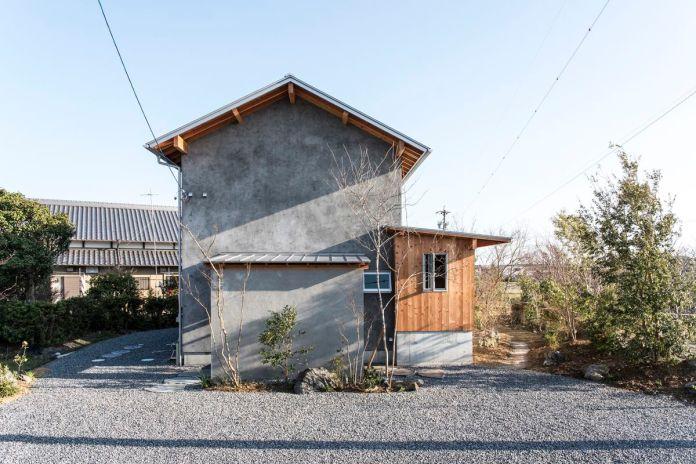 Дом со скатной крышей, облицованный бетоном и деревом.