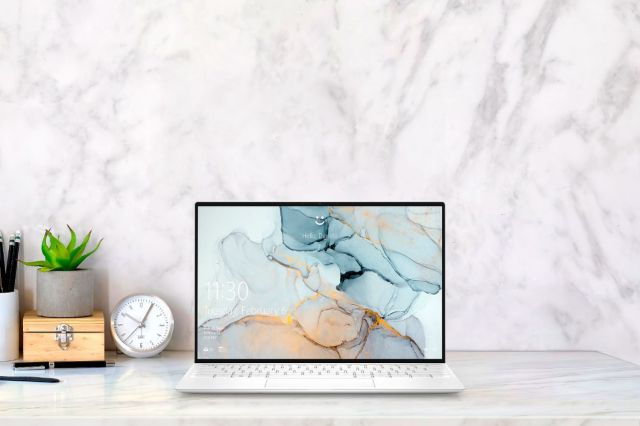 The Dell XPS 13 sits on a desk with a marble background.