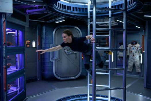 Hilary Swank clings to a ladder in zero gravity in the Netflix series Away